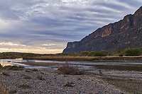 The walls of the Santa Elena Canyon with the rio grande river flowing down towards the gulf.  This side of the canyon is the Mexico side. You see catails growing along the river in early morning.