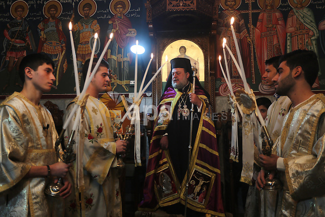 Palestinian Greek Orthodox Christians attend Christmas mass at the Orthodox Saint Porfirios church in Gaza City on January 7, 2016. The Orthodox Church celebrates Christmas and other religious holidays according to the Julian calendar, while other Christian churches have adopted the later Gregorian calendar. Photo by Mohammed Asad