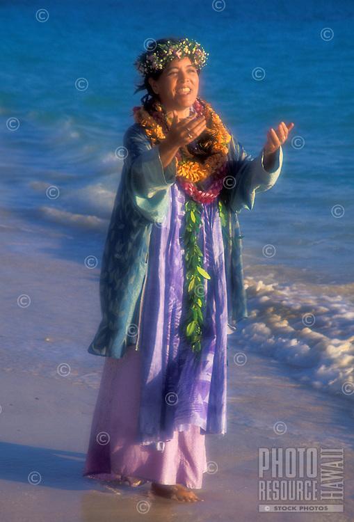Part Hawaiian woman wearing leis chanting ( oii) at sunrise on the beach at Lanikai, Oahu