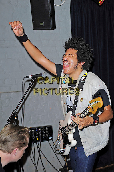 Isaiah Radke of Radkey <br /> performing in concert, The Blackeart, Camden, London, England. <br /> 17th October 2013<br /> on stage in concert live gig performance performing music half length white jean denim jacket sleeveless bass guitar singing mouth open hand arm in air profile <br /> CAP/MAR<br /> &copy; Martin Harris/Capital Pictures