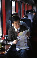Passenger reads a map on the Beijing to Hong Kong long-distance train, Beijing, China.