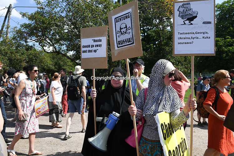 Demonstrators gather in City Park for the Helsinki Calling peace march a day ahead of the summit between US President Donald Trump and Russian President Vladimir Putin in Helsinki, Finland on July 15, 2018.