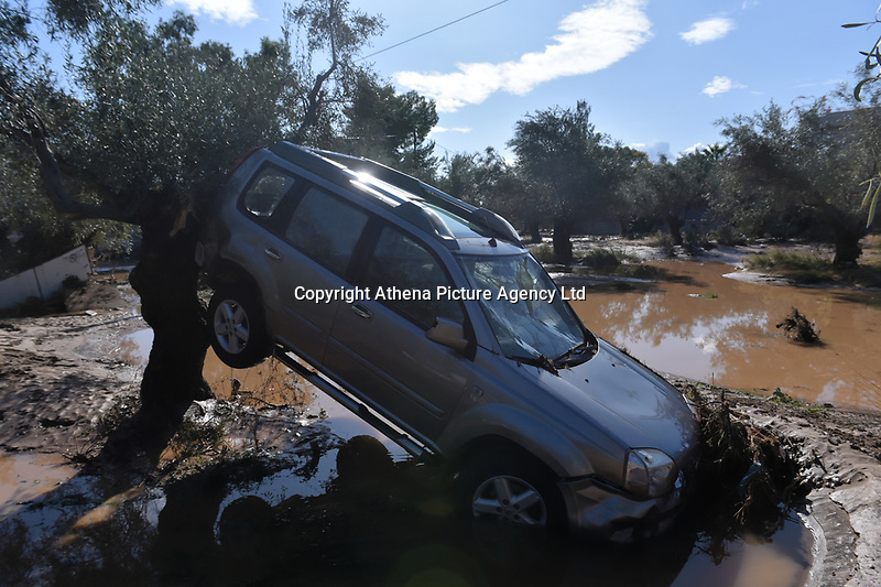 Pictured: A car is resting a against a tree caused by heavy rain in the area of Kinetta, near Athens, Greece. Monday 25 November<br /> Re: Heavy overnight rainfall has caused flooding and landslides in parts of Greece.