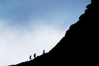 silhouette of people hiking on mountain