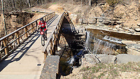 NWA Democrat-Gazette/FLIP PUTTHOFF <br /> Kelly Williams, director of the FAST National Mountain Bike Patrol, crosses a creek along the Back 40 trail system in Bella Vista. Patrol members assist riders with bike repair and first aid.