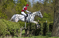 Young man rides a grey mare horse in a cross-country eventing competition, United Kingdom