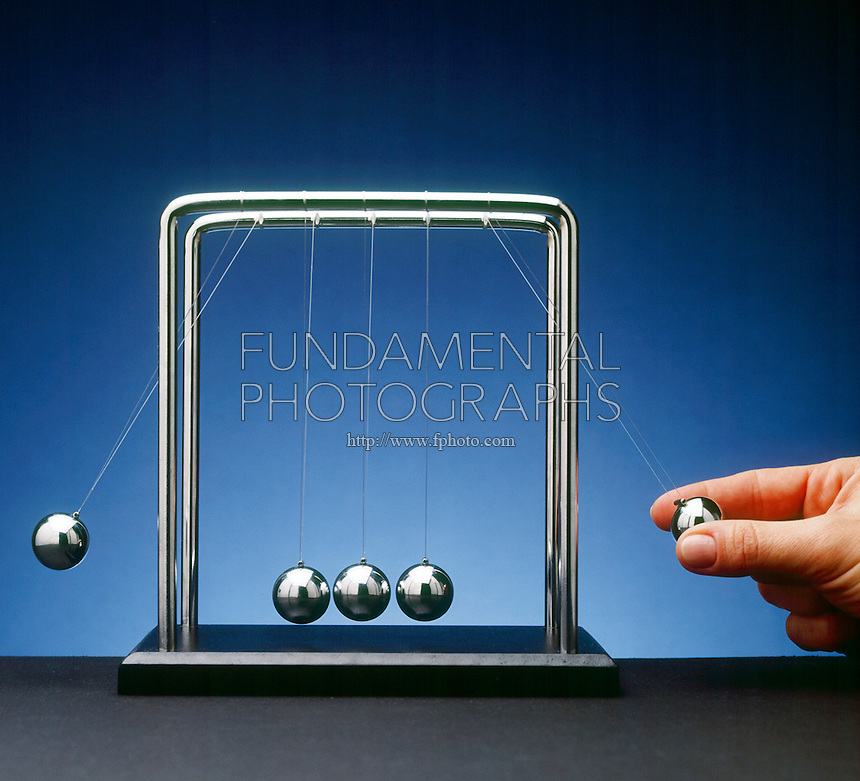 NEWTON TOY PENDULA: COLLISION EXPERIMENT<br /> Newton's Third Law<br /> Conservation of Momentum<br /> A double exposure - One pendulum bob used as a projectile collides with three other  bobs, causing an  displacement of one  bob equal to the original displacement of the projectile bob. The sum of momenta  of an isolated system is a constant.