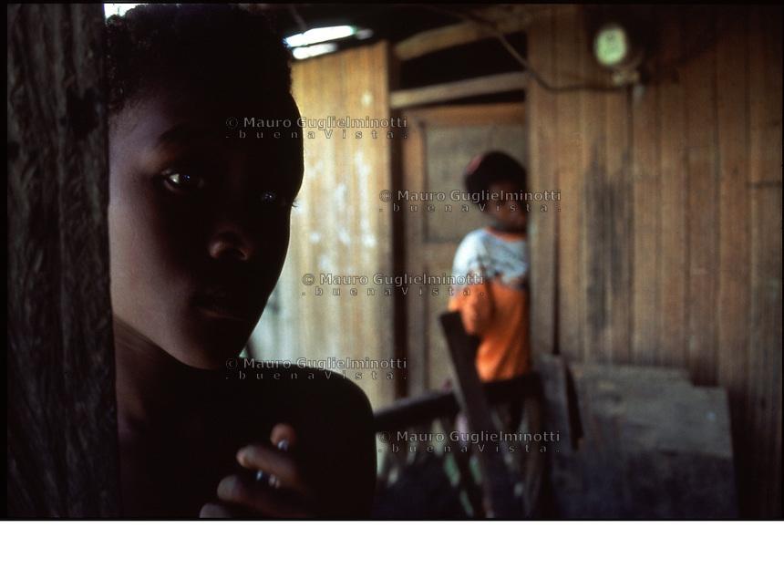 Buenaventura Colombia sguardo di ragazzo, la madre osserva dietro la porta di casa