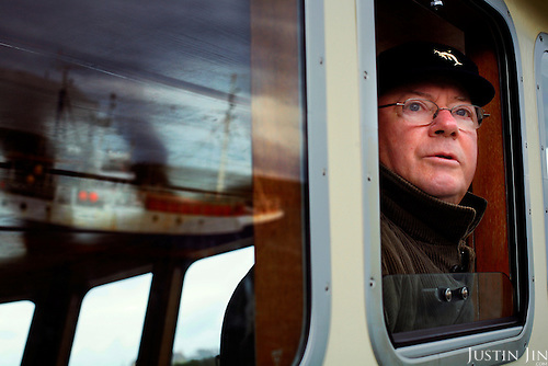 Former fisherman Jimmy O'Flannery drives his boat in  Dingle, on the west coast of Ireland, to bring tourists to the famed dolphin Fungi. O'Flannery is the head of the Dingle Boatmen's Association.In 1984, the lone dolphin was observed escorting the fishing boats. The fishermen named him Fungi. Within months, he had become such a fixture that local officials declared him a permaneint resident. .For more than 20 years, Fungi has stayed in the harbour and befriending humans, becoming one of Ireland's top attractions..Every summer, Dingle town?s 3,000 inhabitants are overrun by tourists, who have come to see Fungi on boat trips..Fungi, a male bottlenose, is around 30 years old. He weighs about 250 kilos and is about four metres in length. .The Dingle Boatmen's Association offers one-hour boat trips out to the harbour mouth every day during the summer. They run throughout the day, as long as there are people to fill the boats. No reservations are needed. They are so confident that Fungie will appear that they offer a money-back guarantee.