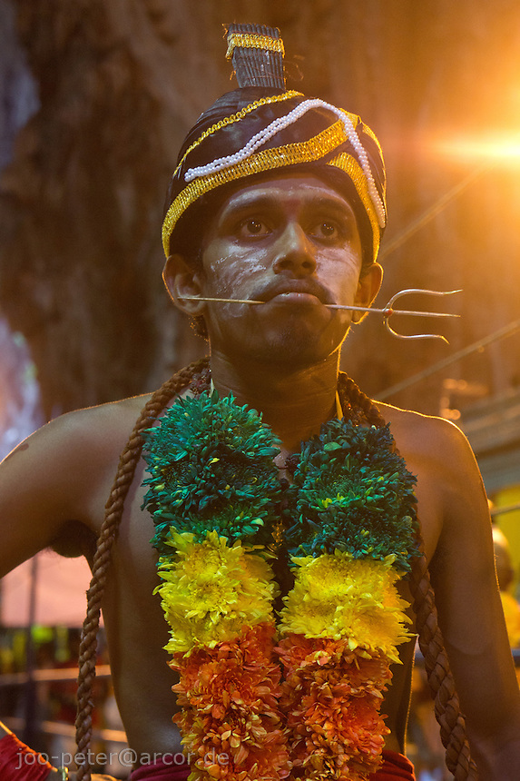 man trance with  Shivas fork-shaped spear thrilled through his cheeks while Thaipusam ceremonies inside Batu Caves, Kuala Lumpur, Malaysia, 2012. Thaipusam ceremonies, celebrated by tamile Hindu community in Malaysia, take place  in Sanctuary of Batu Caves at the border of Kuala Lumpur, each year around end of January or beginning of February, according to Hindu moon calendar. The event is paying hommage to Lord Murugan, a spirit or god created by Shiva to lead the army of gods against the army of evil demons, finally defeating the evil spirits. There are many ways to present offerings or sacrifices for this major religious event. Devotees mortify their bodies by carrying heavy kavaris with spears fixed in their skin or fruits, flowers and little post with holy milk fixed with hooks in their skin, ascending the stairways to the sanctuary in trance, `followed by assistant  taking care and musicians playing loud and fast rhythmic trance music.  Many families shave their head in a ritual before ascending the stairways, as part of rituals to obtain salvation for their ancestors.