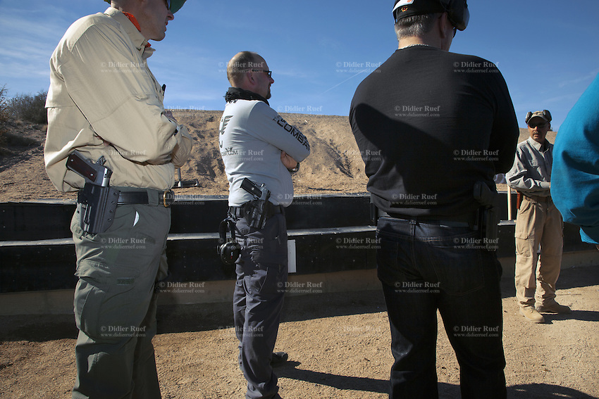 "USA. Arizona state. Paulden town. Gun Site Academy. Gun Site Academy ""teaches responsible, safe and effective use of small arms in self defense "".  A group of men listens to their instructor (R) during the 250 Pistol Class. The 250 Pistol Class includes five solid days of range work and intensive outdoor live fire where people learn how to improve their shooting skills and be in control of their guns and immediate environment. Students emerge stronger, more alert, and conditioned to respond appropriately to any threat. A firearm is a portable gun, being a barreled weapon that launches one or more projectiles often driven by the action of an explosive force. Most modern firearms have rifled barrels to impart spin to the projectile for improved flight stability. The word firearms usually is used in a sense restricted to small arms (weapons that can be carried by a single person). The right to keep and bear arms is a fundamental right protected in the United States by the Second Amendment of the Bill of Rights in the Constitution of the United States of America and in the state constitutions of Arizona and 43 other states. 25.01.16 © 2016 Didier Ruef"