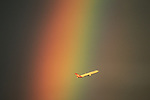 A Qantas jet flys through a rainbow in the sydney sky late one afternoon. Photo: Steve Christo