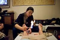 Una ragazza al lavoro in un centro massaggi dei piedi.<br /> A foot massage center
