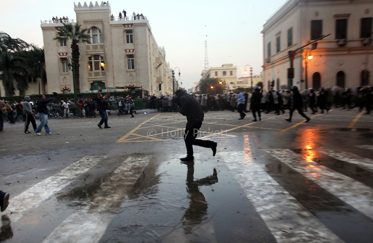 A protester runs during a demonstration in downtown Cairo, Egypt, Jan. 25, 2011. The day was an official holiday in honor of the achievements of police, but thousands of demonstrators came out to protest corruption, unemployment and police torture.