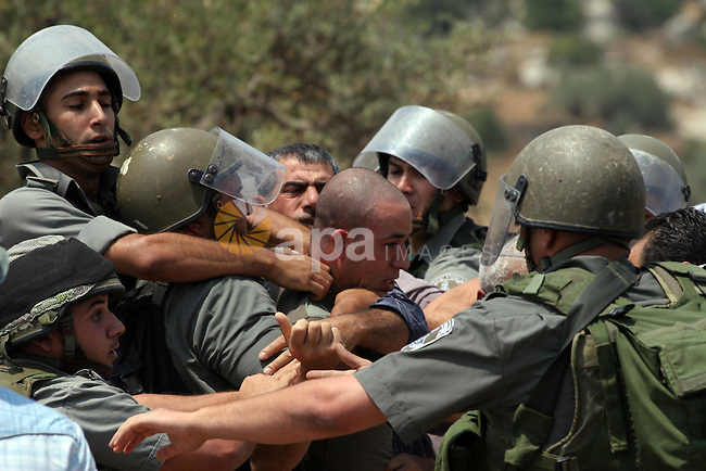 Israeli soldiers scuffle with Palestinian and international protestors during a demonstration against the construction of the controversial Israeli cement barrier in the West Bank village of Nilin near Ramallah. Sixteen Palestinians and one Israeli were lightly wounded today when Israeli security forces dispersed a protest against the West Bank separation barrier, Palestinian medics said.