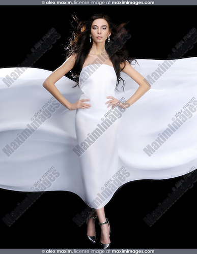 Beautiful young woman in wrapped in white flowing fabric shining on black background