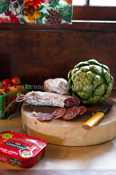 Kitchen countertop in a rustic cabin. Close up on cutting board with sliced salami, an artichoke, and a knife. Beside it are cherry tomatoes and a can of sardines.