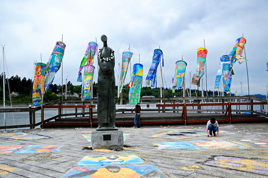 During the Wooden Boat Fair, there was an interactive Mother's Day art activity around the Motherhood statue.  Passers-by were encouraged to decorate the boardwalk with colored chalk and also to cast their intentions for their mothers by casting a handful of grain onto it as well.  Percival Landing, Olympia, Washington, USA