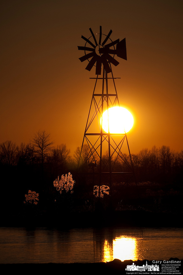 Windmill silhouetted against setting sun on a farm in Ohio.