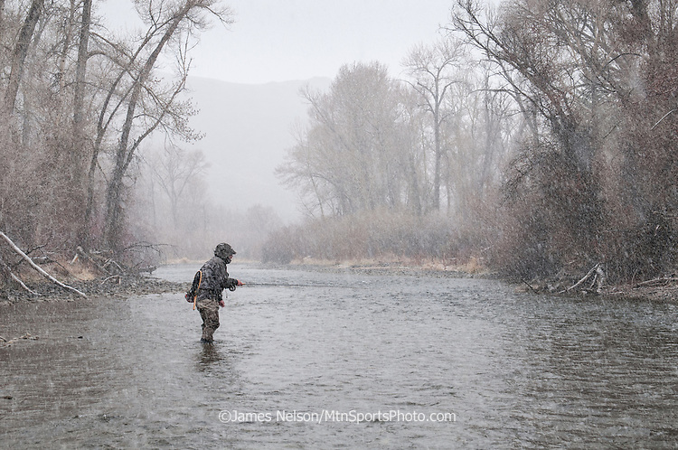 An angler fly fishes for trout during a snow storm on the Big Lost River, Idaho.