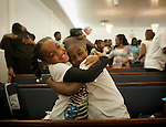 LOS ANGELES,CA - JANUARY 18,2009:  Jalynn Harris,7, left, and Terran Artis,9 embrace during church services at Faith Inspirational Missionary Baptist Church, in Compton January 18, 2009. Feature on local efforts to combat murders, violent crime and gang-related crime, and the campaign to improve the relationship between law enforcement and the community. Faith Inspirational Missionary Baptist Church is very active in working to improve the community relations between Compton's black and latino residents.