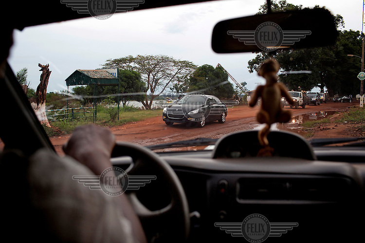 The cavalcade of CAR president Catherine Samba-Panza, seen through the windscreen of a passing taxi, as it passes along an unpaved road in the capital. In late 2012 after years of instability and conflict, the Seleka, a predominantly Muslim rebel group, fuelled by grievances against the government, overran the country and, In March 2013, ousted President Francois Bozize, who fled the country. The rebel's leader Michel Djotodia was proclaimed president in August 2013. He disbanded the Seleka in September 2013 but law and order collapsed and ex-Seleka fighters roamed the country committing atrocities against the civilian population. In an attempt to defend their lives and property vigilante groups, calling themselves Anti-Balaka (Anti-Machete), formed to confront the ex-Seleka fighters but soon began to take reprisals against the wider Muslim population and the conflict became increasingly sectarian. By December 2013, with international fears of a genocide being voiced, French led peacekeepers deployed to the country began to act on a UN mandate to disarm the fighters and protect the civilian population. However, they have struggled to contain the situation. Much of the Muslim population, in particular, have been forced into ghettos where they are suffering from food shortages and limited access to healthcare. Often, only a few peacekeepers stand between them and a massacre by vengeful Anti-Balaka militants. UN reports describe 'thousands' killed, while over 600,000 people have been internally displaced and a further 200,000 have fled the county.