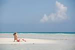 Grand Bahama Island, The Bahamas; a woman in a red bikini sits on a sandbar along the deserted shoreline of Gold Rock Beach, late afternoon at low tide, part of the Lucayan National Park