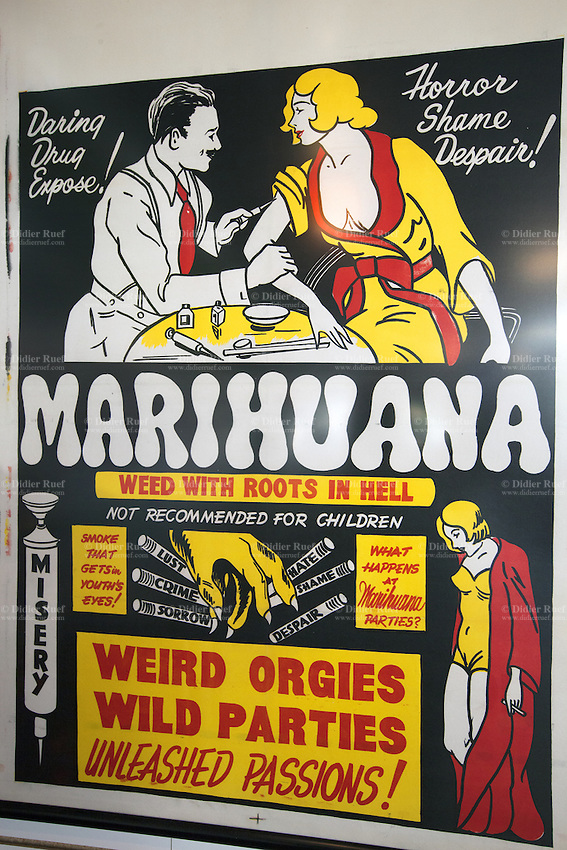 "USA. Washington state. Seattle. Movie's poster on the wall at Uncle Ike's. The striking graphic poster is an advertisement for the 1936 film ""Marijuana: Weed with roots in Hell "" which touts cannabis influence on youth inevitable downslide into weird orgies, wild parties, unleashed passions, lust, crime, sorrow, shame, hate, despair and misery. The film is a cautionary tale against using the drug, as all who come into contact with it are affected, thus losing themselves and committing depravities. Uncle Ike's is authorized, according to cannabis legalization in Washington State, to sell marijuana as a retail store front. Uncle Ike's carries a wide variety of cannabis flowers, edibles, and concentrates for recreational marijuana. Cannabis, commonly known as marijuana, is a preparation of the Cannabis plant intended for use as a psychoactive drug and as medicine. Pharmacologically, the principal psychoactive constituent of cannabis is tetrahydrocannabinol (THC); it is one of 483 known compounds in the plant, including at least 84 other cannabinoids, such as cannabidiol (CBD), cannabinol (CBN), tetrahydrocannabivarin (THCV), and cannabigerol (CBG). 13.12.2014 © 2014 Didier Ruef"