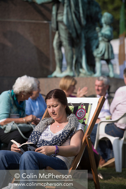 A woman reading a book as crowds gather for the last day of the Edinburgh International Book Festival. The three-week event is the world's biggest literary festival and is held during the annual Edinburgh Festival. The 2013 event featured talks and presentations by more than 500 authors from around the world and was the 30th edition of the festival.