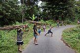 INDONESIA, Flores, young children carry wood down a road to their home in Dintor village
