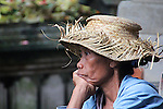 A beautiful straw hat shades a woman resting during her shopping trip to main market at Ubud, Bali