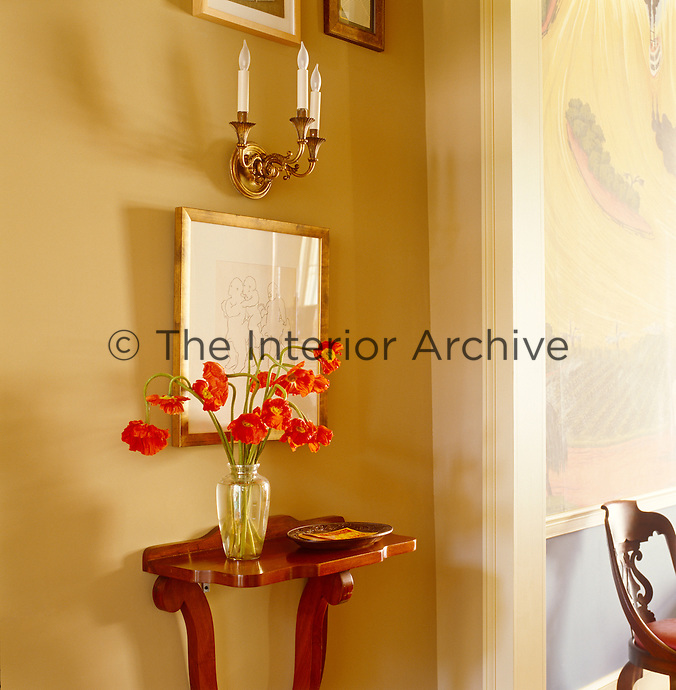 A vase of red flowers echoes the colours of the scenic wallpaper in the living room