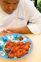 Portrait of chef Gennaro Esposito tasting a dish of freshly cooked pomodorino piennolo del Vesuvio tomatoes