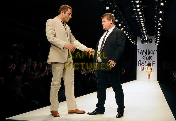 DAVID WALLIAMS & JAMES CORDEN.The Fashion For Relief Haiti 2010 show for London Fashion Week Autumn/Winter 2010 at Somerset House, London, England..February 18th, 2010.LFW catwalk runway full length black beige suit profile holding hands pink shirt white funny .CAP/CAS.©Bob Cass/Capital Pictures.