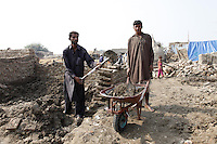 Two men clear the mud and debris that is all that remains of their home, in a village in rural Sindh, Pakistan.<br /> <br /> The spade and wheelbarrow they use has been provided by UKaid from the Department for International Development, as part of a package of support for families that were displaced by the floods in 2010. <br /> <br /> Find out more about the UK government's response to the Pakistan floods at www.dfid.gov.uk/pakistan-floods-six-months ( http://www.dfid.gov.uk/pakistan-floods-six-months ) <br /> <br /> Image: DFID/Russell Watkins<br /> <br /> Terms of use<br /> <br /> This image is posted under a Creative Commons - Attribution Licence ( http://creativecommons.org/licenses/by/3.0/ ) , in accordance with the Open Government Licence ( http://www.nationalarchives.gov.uk/doc/open-government-licence/ ) . You are free to embed, download or otherwise re-use it, as long as you credit the source as 'Department for International Development'.