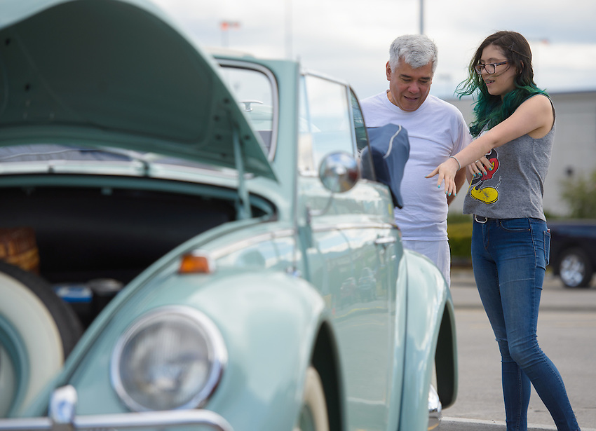 Car lover Gabriella Nunez shows her father, Edwardo Nunez, around the 11th Annual VW Family Reunion Car Show at the Dimond Center.