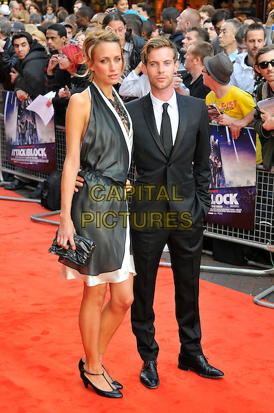 "RUTA GEDMINTAS & LUKE TREADAWAY.Attending the UK Film premiere of ""Attack The Block"", Vue West End, Leicester Square, London, England, UK, May 4th 2011..full length grey gray suit white shirt black tie dress  necklace halterneck clutch bag  t-bar shoes .CAP/CAS.©Bob Cass/Capital Pictures."