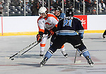 OMAHA, NE - FEBRUARY 9:  Connor Chatham #9 from the Omaha Lancers pushes the puck past a pair of defenders including Zach Frye #21 from the Lincoln Stars in the first period at the Battle on Ice Saturday at TD Ameritrade in Omaha, NE. (Photo by Schyler Eggen/Inertia)