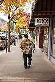 USA, Oregon, Ashland, a man carries his baby under his arm and walks down the sidewalk on East Main street in downtown