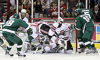 UNO's Johnnie Searfoss goes airborne during a scramble in front of Bemidji State goalie Dan Bakala. Bemidji State beat UNO 4-2 Friday night during the first round of the WCHA playoffs at Qwest Center Omaha. (Photo by Michelle Bishop)