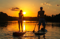 View of a couple's silhouette on stand-up paddle boards during a beautiful golden sunset on Lady Bird Lake in downtown Austin, Texas.