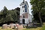 Foto: VidiPhoto<br /> <br /> SLIJK-EWIJK – Medewerkers van afbouwbedrijf Stöteler uit Groenlo verwijderen woensdag het stucwerk aan de buitenzijde van het karakteristieke witte kerkje aan de Waaldijk bij Slijk-Ewijk. Het Rijksmonument uit de 14e eeuw herbergt sinds enkele jaren een kunstgalerie, maar wordt nog steeds gebruikt voor rouw- en trouwdiensten. Na de samenvoeging van de protestantse gemeenten van Slijk-Ewijk en Herveld besloot de kerkenraad het kleinste gebouw af te stoten. Door ophoping van vocht in de muren laat het pleisterwerk -dat in de jaren zeventig is aangebracht- aan de buitenzijde los en moet nu vervangen worden. Gekozen is voor een 'ademende'kalmortellaag. Om het effect te kunnen beoordelen wordt eerst een proefstrook aan de voorzijde van de toren behandeld.