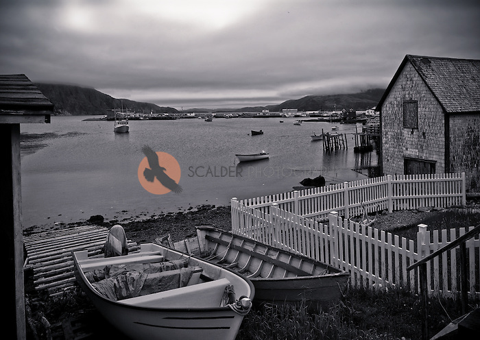 small fishing harbor in Newfoundland with a storm approaching, photo is black and white
