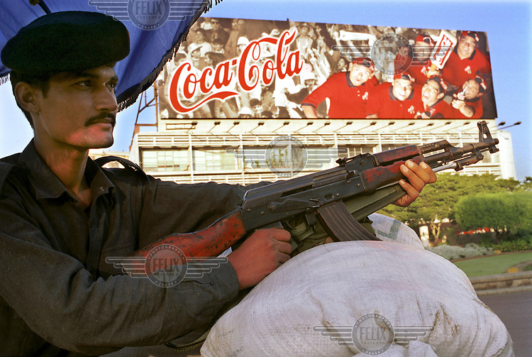 © Piers Benatar / Panos Pictures..Karachi, Pakistan. 23 October 2001...A policeman armed with a rifle stands guard on the street, with a billboard advertising Coca Cola in the background. It illustrates the contradictions which exist in Pakistan, where fundamentalist Islam is battling for supremacy with the forces of globalisation and the West.