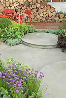 Chives in bloom, lady's mantle, foliage plants, Heuchera, deck, patio, firewood log pile, red chairs for a pretty and fresh spring garden scene