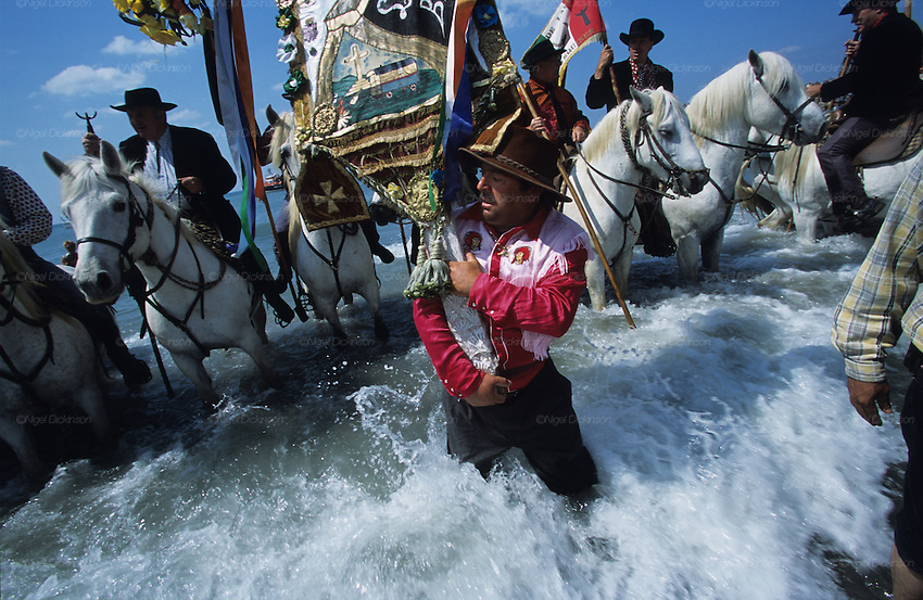 José LaFleur, a Manouche, carries the Gypsy standard into the sea, during the Gypsy pilgrimage of Saintes Maries de la Mer. Camargue, France