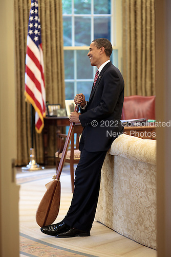 Washington, DC - June 26, 2009 -- United States President Barack Obama stands in the Oval Office with a Hawaiian paddle that was given to him as a gift by Chef Allen Wong, who catered the 2009 Presidential Luau, June 26, 2009..Mandatory Credit: Pete Souza - White House via CNP