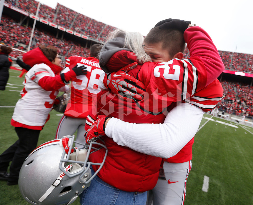 Ohio State Buckeyes kicker Drew Basil (24) embraces family as nineteen seniors were recognized before Saturday's NCAA Division I football game against Indiana at Ohio Stadium in Columbus on November 23, 2013. (Barbara J. Perenic/The Columbus Dispatch)