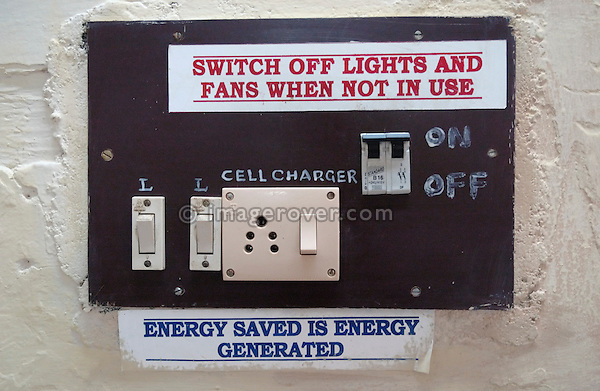"""India, Tamil Nadu, Ooty (Udhagamandalam) 2005. Electrical switches and socket in Ooty railway station with signs reading """"switch of lights and fans when not in use"""" and """"energy saved is energy generated""""."""
