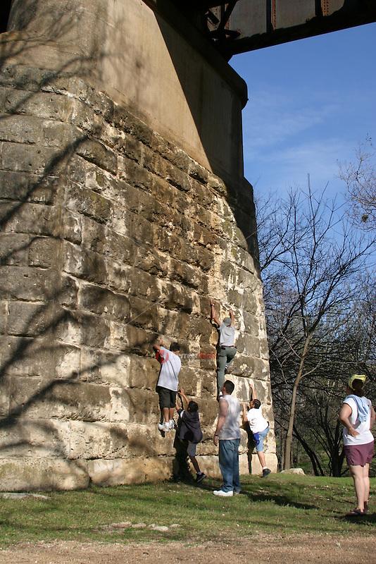 Austinites enjoy climbing the brick steps on the pillars of the Union Pacific Railroad Bridge on town lake in austin.